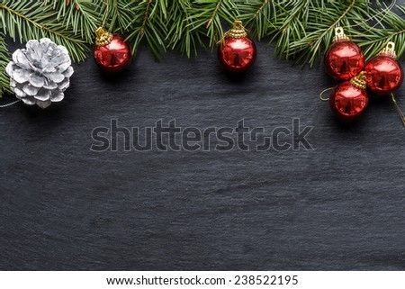 Christmas background with colorful red baubles, a silver decorative pine cone and green pine branches over a textured grey background with copy space for your seasonal greeting - stock photo
