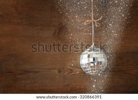 christmas background with decoration hanging on a rope over wooden background. glitter overlay  - stock photo