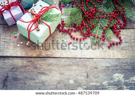 Christmas background with decorations and gift boxes on wooden board/toned photo
