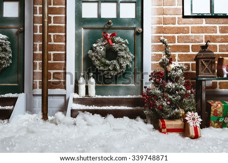 Christmas background with door, brick wall, street light, snow and christmas tree