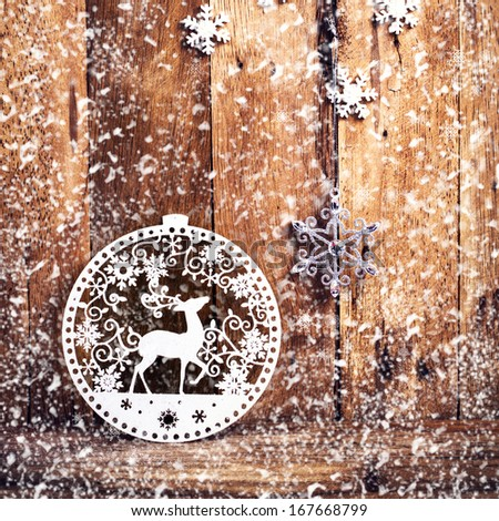 Christmas background with festive decorations and falling snow over wooden wall. Vintage Christmas card or invitation with copyspace. - stock photo