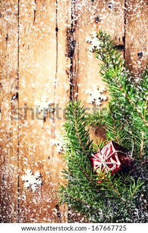 Christmas background with festive ornaments, red gift box and fir branches with falling snow over wooden wall. Vintage holiday card or invitation with copyspace. - stock photo