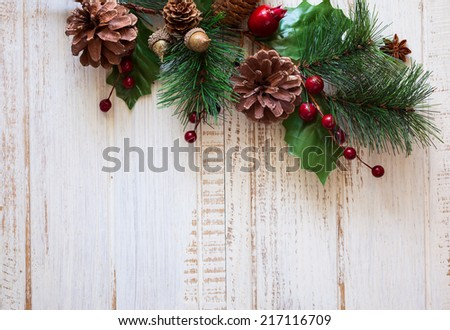 Christmas background with fir branches,pine cones and berries on the old wooden board - stock photo