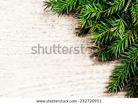 Christmas background with fir twigs. Christmas rustic background - vintage planked wood with pine brunch  - stock photo