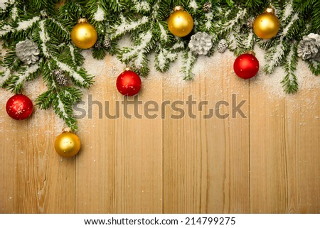 Christmas background with fresh firtree and  baubles on wood with bright snow  - stock photo