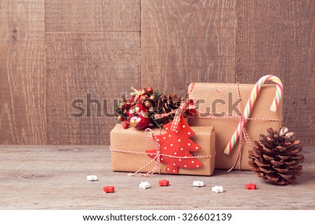 Christmas background with gift boxes and rustic decorations on wooden table - stock photo