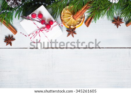 Christmas background with gift, fir tree brunches and spices at white wooden table. Top view, copy space - stock photo