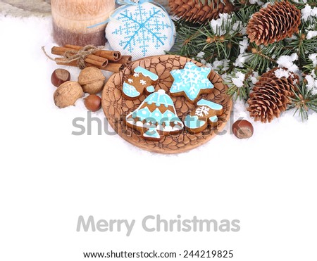 Christmas background with ginger cookies on a clay plate and branches of a Christmas tree.
