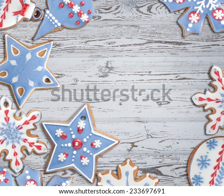 Christmas background with gingerbread cookies decorated with royal icing against bleached wooden board. Would make a beautiful greeting card. - stock photo