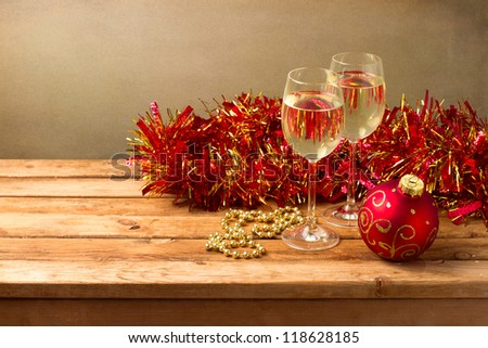 Christmas background with glasses of wine and ornaments on wooden table - stock photo