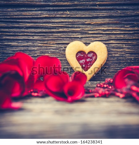 Christmas Background with Heart-shaped Cookies (sweets) with Red Rose Petals on a Vintage Wooden Background - stock photo