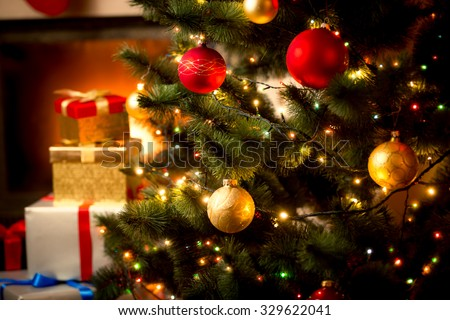 Christmas background with illuminated fir tree and fireplace at house - stock photo