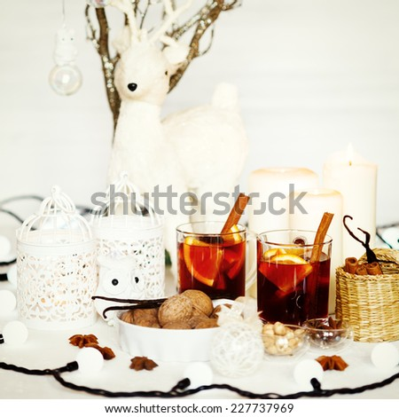 Christmas background with mulled wine, walnuts, candles and white decorations. Shallow dof, selective focus. Image toned in instagram vintage colors. - stock photo