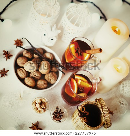 Christmas background with mulled wine, walnuts, candles and white decorations. Shallow dof, selective focus. Instagram vintage colors. - stock photo