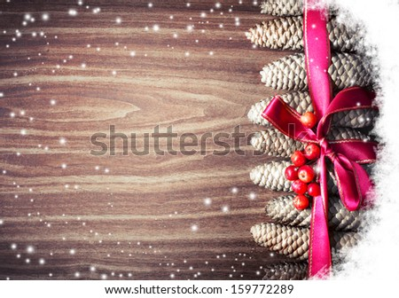 Christmas background with pinecones and a red Christmas ribbon/  Christmas decoration with Pine Cone and snow/Christmas ornaments pine cones  on a brown wood panel - stock photo