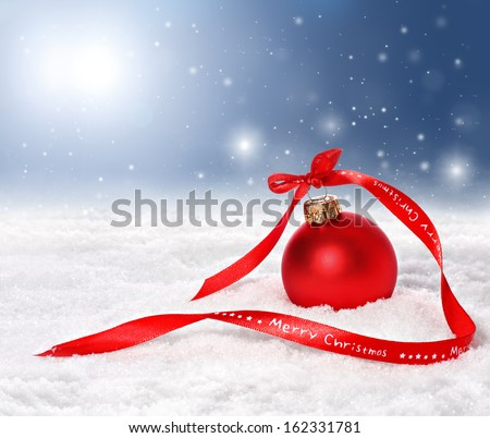 Christmas background with red bauble and merry christmas ribbon on snow with snowflakes falling from a blue sky - stock photo