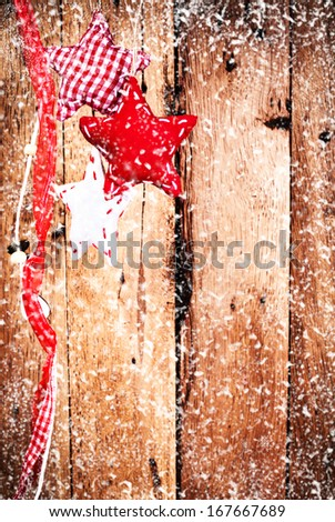 Christmas background with red ornaments and  falling snow over wooden wall. Vintage holiday card or invitation with copyspace. - stock photo
