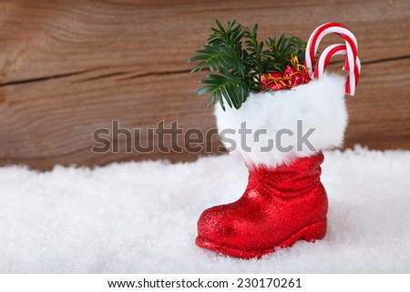 christmas background with santa boot and candy cane and gifts inside - stock photo