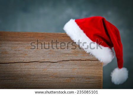 christmas background with santas hat on a wooden board - stock photo