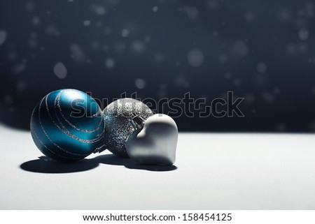 christmas background with shiny christmas ornaments on white surface with dark background - stock photo