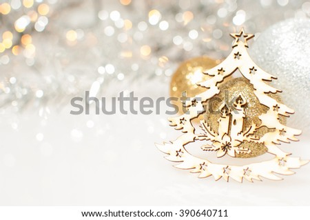 Christmas background with silver and gold Christmas balls and wooden carved Christmas tree with candles. - stock photo