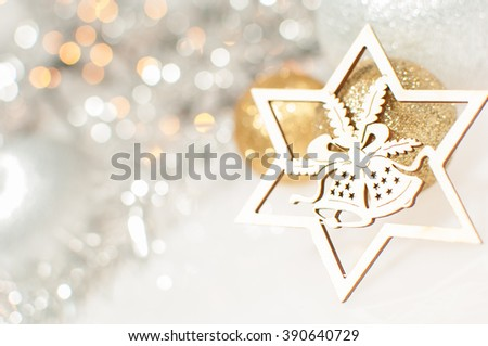 Christmas background with silver and gold Christmas balls and wooden carved star with jingle bells. - stock photo