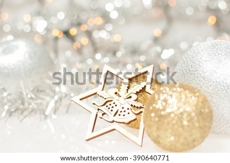 Christmas background with silver and gold Christmas balls and wooden carved star with jingle bells.