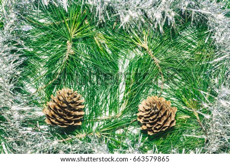 Christmas background with silver decoration, pinecones and green pine leaves. Copy space for text