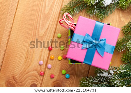 Christmas background with snow fir tree, gift box and candies. View from above with copy space - stock photo