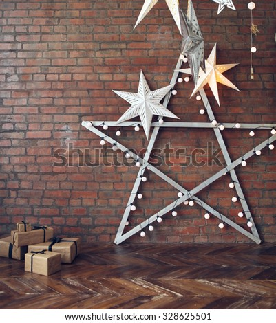 Christmas background with stars and presents over brick wall - stock photo