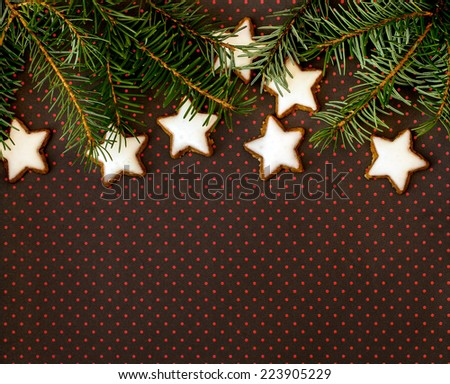 Christmas background with twig of fir tree and cinnamon stars on brown background with dots - stock photo