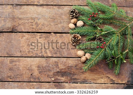 Christmas background with walnut, pine cone, holly berry and fir branches - stock photo
