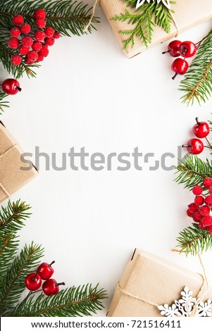 Christmas background with xmas tree, gift boxes and red berries on white wooden background. Merry christmas greeting card, frame, banner. Winter holiday theme. Happy New Year. Flat lay.