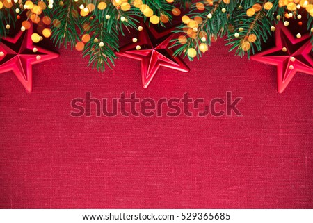 Christmas background with xmas tree, red ornaments and glowing golden bokeh lights on red canvas background. Merry christmas card. Winter holiday theme. Happy New Year. Space for text