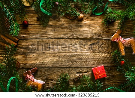 Christmas background.Xmas wreath card with with copyspace on wooden background. Christmas ornaments on wood with candy and ribbons. - stock photo
