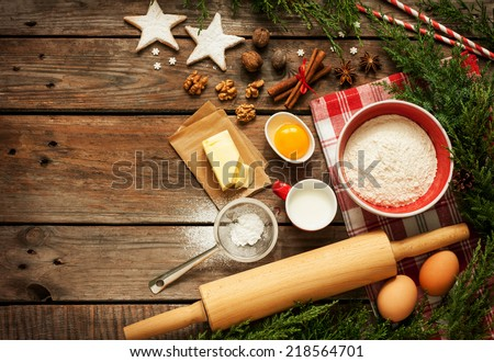 Christmas - baking cake background. Dough ingredients and decorations on vintage planked wood table from above. Rural kitchen layout with free text space. - stock photo