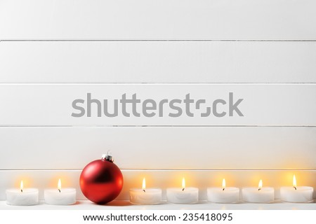 Christmas ball and burning candles on wood background - stock photo