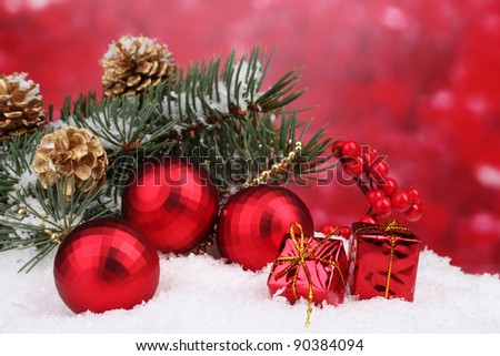 Christmas ball and green tree in the snow on red - stock photo