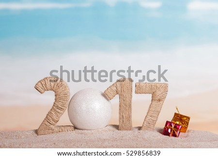 Christmas ball and the inscription 2017 in the sand against the sea