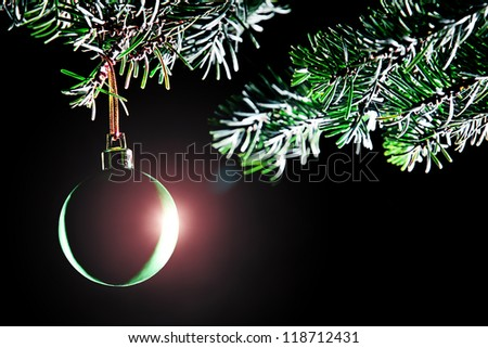 Christmas ball. Decoration xmas tree branch with bauble isolated on black - stock photo