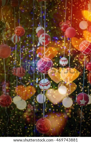 Christmas ball hanging on a Christmas tree with defocused lights ,hearts bokeh , love concept