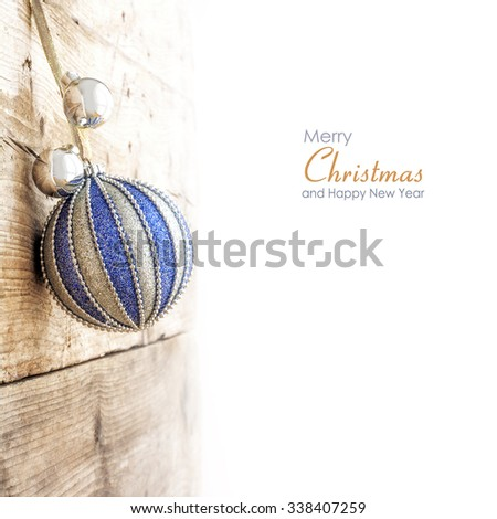 Christmas ball in blue and silver hanging at a wooden wall, border background faded to white, copy space with sample text Merry Christmas and Happy New Year - stock photo
