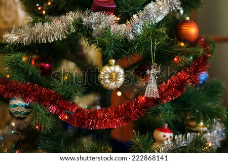 Christmas ball in shape of sunflower on Christmas tree. Christmas tree and light garland on background. Shallow depth of field. Focused on ball - stock photo
