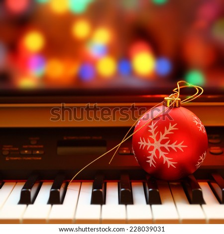 Christmas ball on piano keys - stock photo