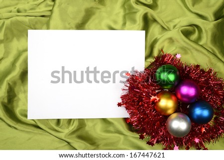Christmas ball on the green satin background. Christmas background concept. You can put your design on the paper