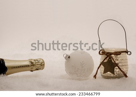 Christmas ball,  wind candle, champagne bottle in snow, evening - stock photo