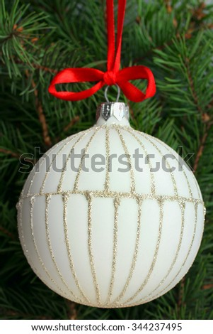 Christmas ball with red ribbon hanging on fir twig - stock photo