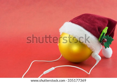 Christmas ball with Santa's hat and earphones, on red with copy-space - stock photo
