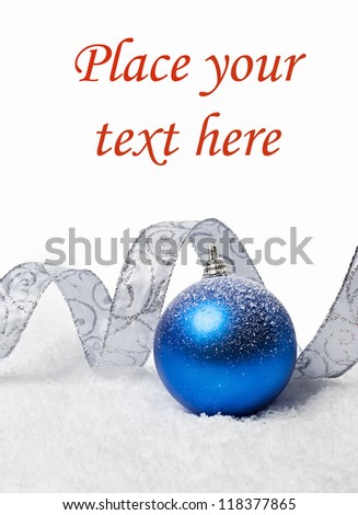 Christmas ball with snow with silver ribbon over white background