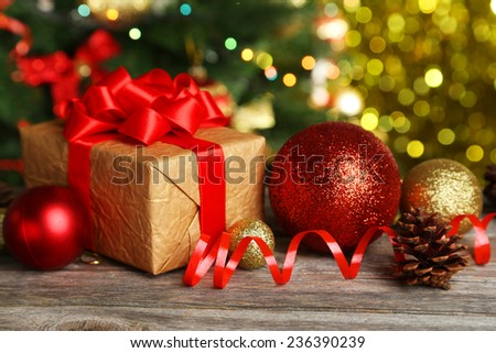 Christmas balls and Christmas gift on grey wooden background